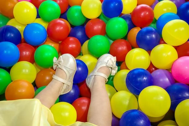 子供たちは遊び場の楽しいパーティーでカラフルなボールに足を踏み入れます