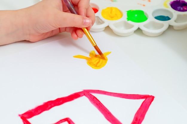 아이의 흰색 종이 손에 수채화로 빨간 집으로 노란 태양을 그리는 차일드 손