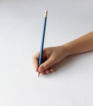 コピースペースと白い背景の上の青い鉛筆を持っている子供の手