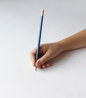 Childs hand holding a blue pencil on a white background with copy space