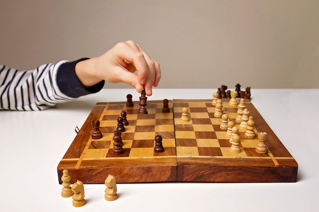 Childs hand holding chess figure while playing education game lifestyle concept