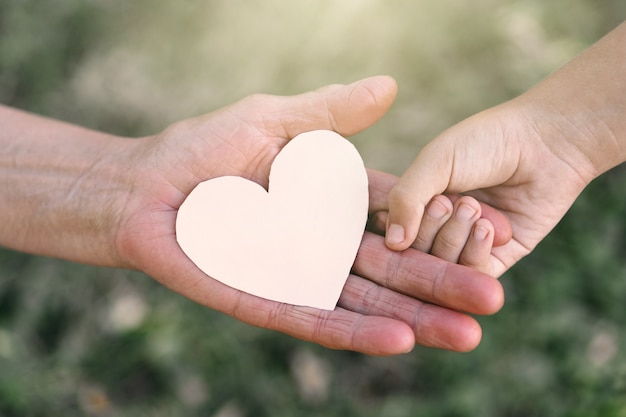 Childs hand and old hand grandmother hold heart. concept idea of love family protecting children and elderly people grandmother friendship togetherness