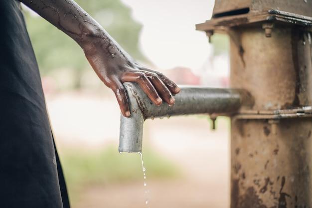 Рука чайлдса на изливе воды в уганде, африка