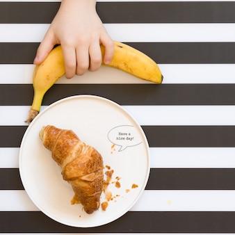 子供の手は白いプレートとフレンチクロワッサンでストライプの背景からバナナを取ります