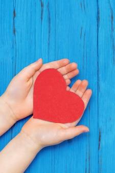 青い木製の背景に手作りの紙の赤いハートを持っている子供の手ヘルスケア家族保険