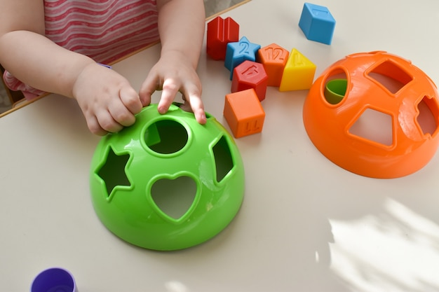 The childs hands play with colorful plastic geometric shapes at the table the kid has fun with the constructor early learning  educational toys