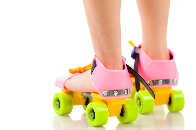 Childs legs in colorful funny rollers over white background