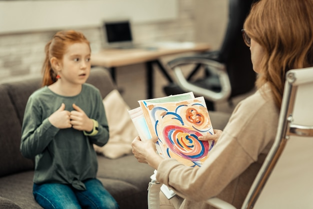 Childs painting. selective focus of a professional female psychologist holding a childs painting