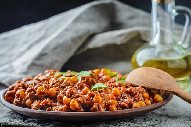 Chile with pork and chickpeas on a plate on dark background