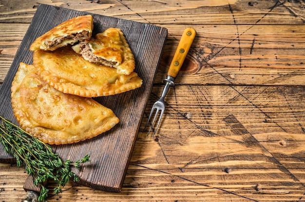 나무 도마에 다진 쇠고기 고기로 채워진 칠레 튀김 엠파 나다