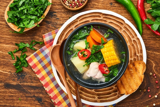 오래된 나무 테이블 배경에 호박, 옥수수, 신선한 고수, 감자를 넣은 칠레 고기 수프. 카수엘라. 라틴아메리카 음식.