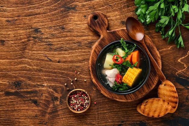 Чилийский мясной суп с тыквой, кукурузой, свежим кориандром и картофелем на фоне старого деревянного стола. казуэла. латиноамериканская еда.