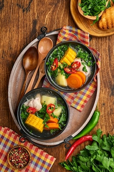 Chilean meat soup with pampkin, corn, fresh coriander and potatoes on old wooden table background. cazuela. latinamerican food.