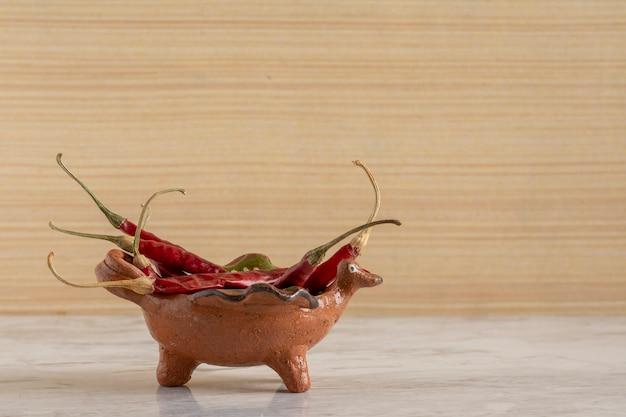 Чили де арбол или сушеный красный перец чили в глиняном горшочке на сером мраморном бруске