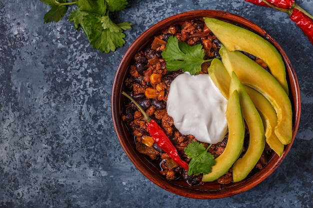 Chili con carne in bowl with avocado and sour cream