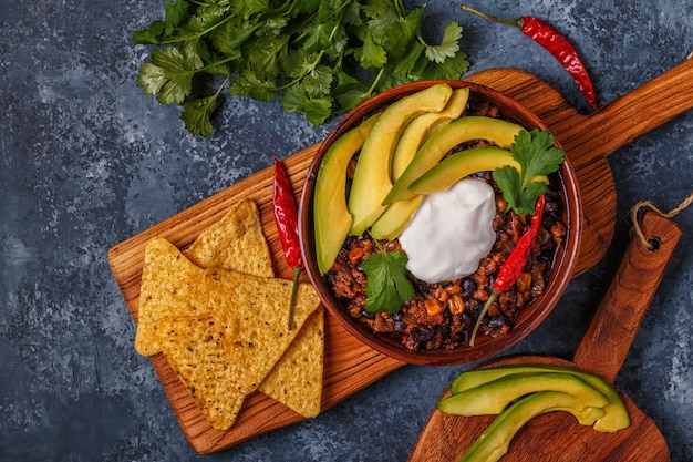 Chili con carne in bowl with avocado and sour cream.
