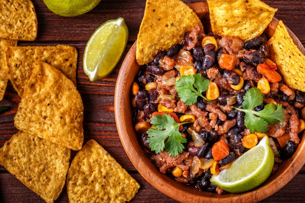 Chili con carne in bowl with tortilla chips on wooden