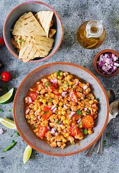 Чили кон карне из индейки с нутом, подается с начос. чили с мясом, начос, лаймом, острым перцем. мексиканская / техасская традиционная еда. вид сверху