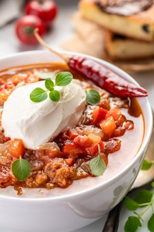 Chili con carne. traditional recipe. large portion of stew with beans, hot peppers, spices and fresh herbs. a large portion is served in a bowl with fresh sour cream.