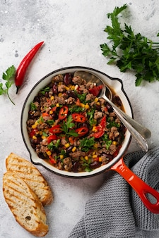 Chili con carne with minced meat and vegetables stew in tomato sauce in a cast iron pan on light gray slate or concrete surface