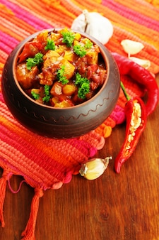 Chili corn carne - traditional mexican food, in pot, on napkin, on wooden