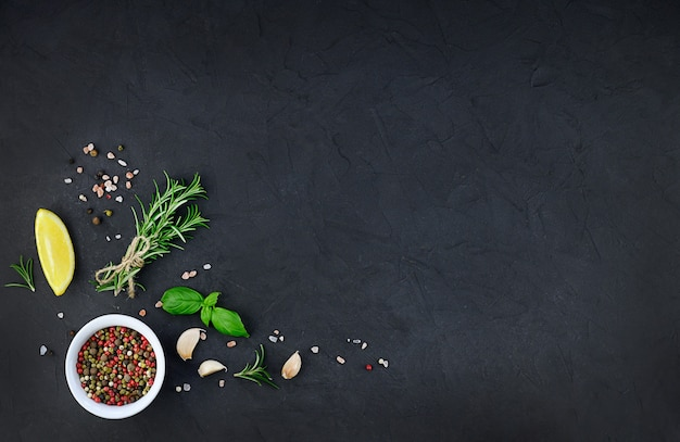 Chili, garlic, oil and spices on black background