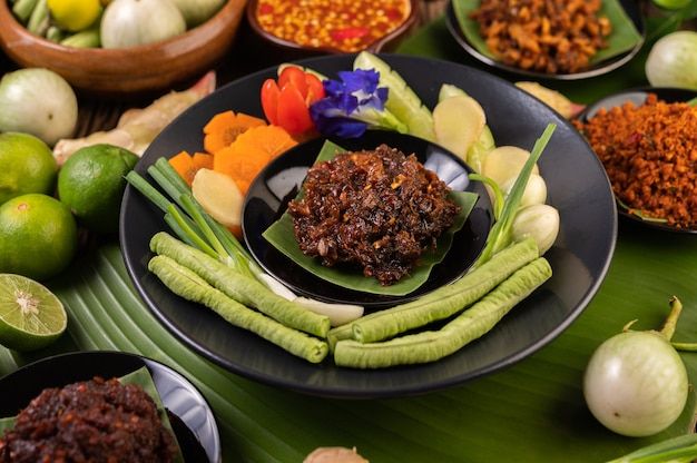 Chili paste is served on banana leaves on a plate with long beans, lime, chili, and eggplant.