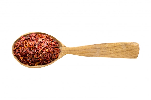 食品に加えるための唐辛子フレーク。白で隔離される木のスプーンでスパイスします。