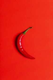 Chili pepper isolated on red, top view