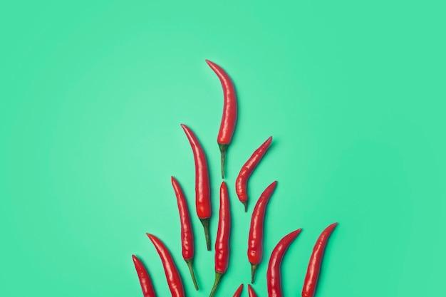 色付きの緑の背景に唐辛子。アジア料理とメキシコ料理とスパイスの材料としてのレッドホットチリペッパー