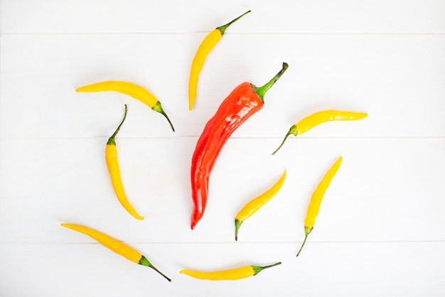 Chili peppers of red and yellow color on  white wooden background.
