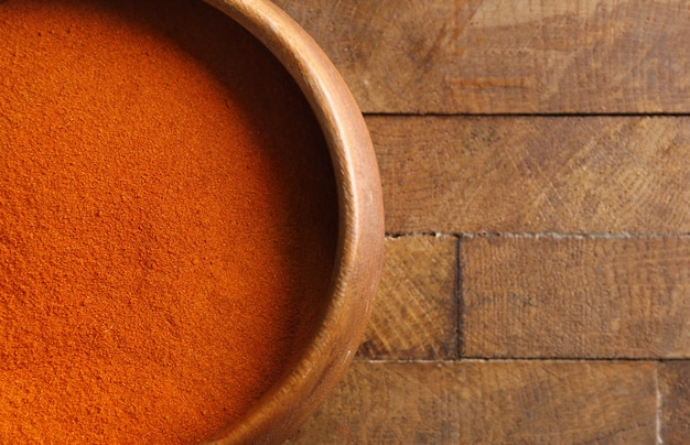 Chili powder in bowl on wooden