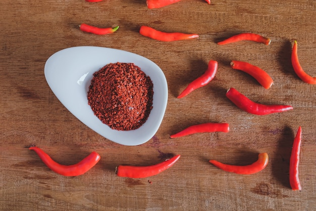 Chili powder and fresh peppers on old wood table.