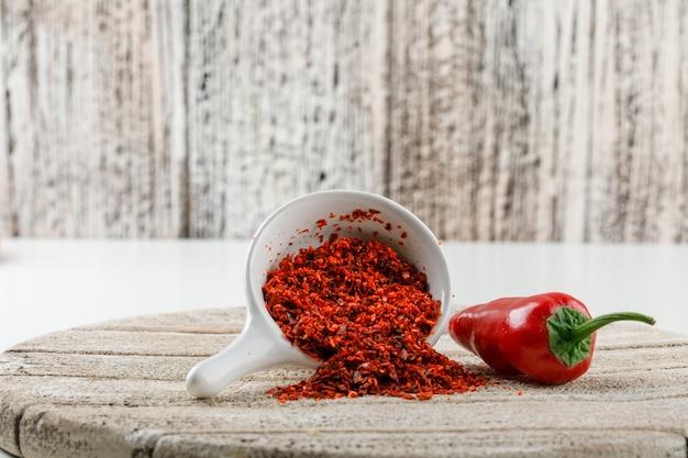 Порошок chili с красным перцем и деревянной частью в белом ветроуловителе на белой и деревянной стене grunge, взгляде со стороны.