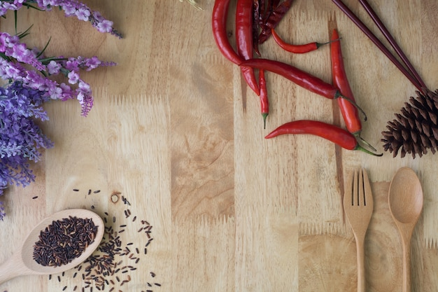 Chili ,rice and spoon wooden on wooden background