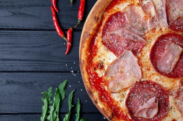 Пицца взгляд сверху с салями, chili горячего перца, ветчиной и сыром на темной деревянной предпосылке. скопируйте sapce для дизайна. продовольственный фон. итальянская кухня. плоская кладка еды