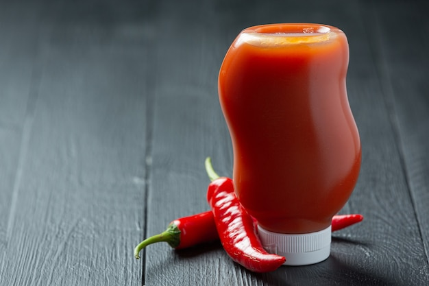 Chili sauce in bottle and peppers on dark wooden surface