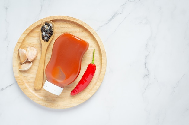 Chili sauce in bottle and peppers on wooden surface