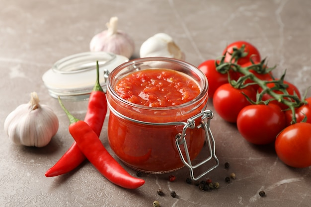Chili sauce in glass jar and ingredients on grey, close up