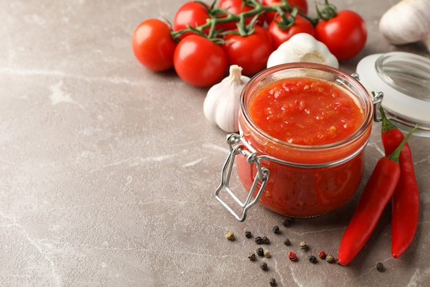Chili sauce in glass jar and ingredients on grey, space for text