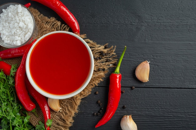 Chili sauce and peppers on dark wooden surface