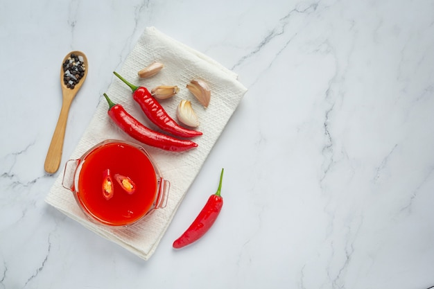 Chili sauce and peppers on white surface