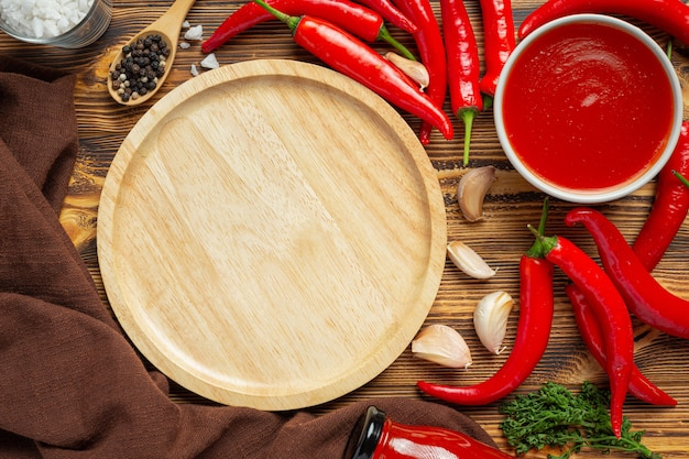 Chili sauce and peppers on wooden surface