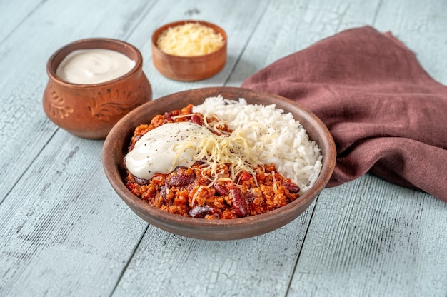 Chili with meat served with rice, grated cheese and tortilla chips
