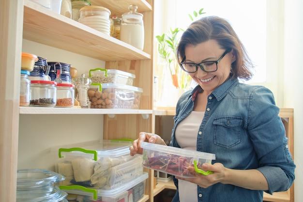 Женщина в кладовке держа контейнер с красным горьким перцем chili. шкаф для хранения на кухне