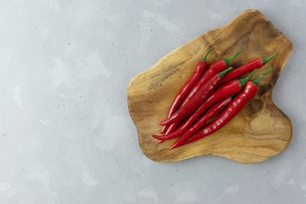 Стручки свежих краснокалильных перцев chili лежат на деревянной доске на серой предпосылке. мексиканская приправа. место для вашего текста.
