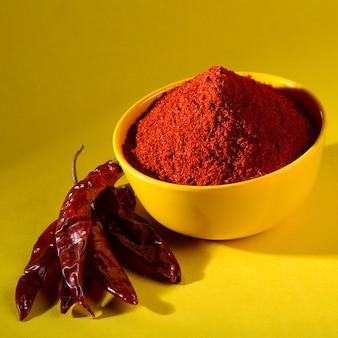 Порошок chili в желтом шаре на желтой предпосылке. красный перец чили