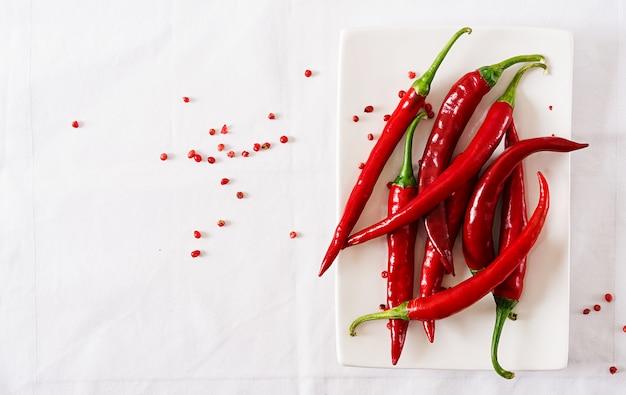 Краснокалильные перцы chili в плите на белой таблице. вид сверху. плоская планировка