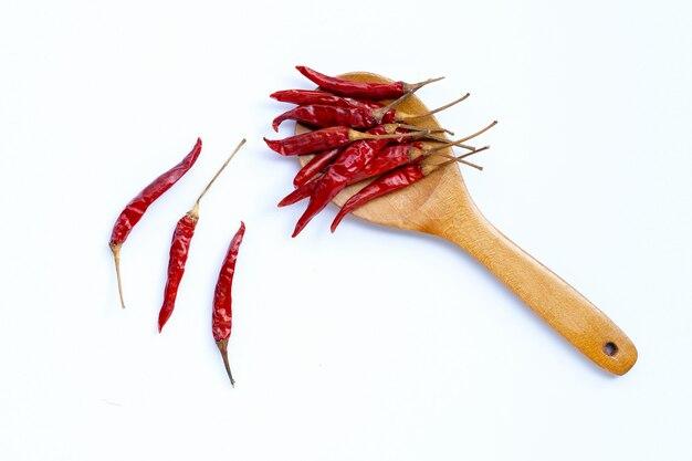 Сухие краснокалильные перцы chili на деревянной ложке на белой предпосылке. копировать пространство