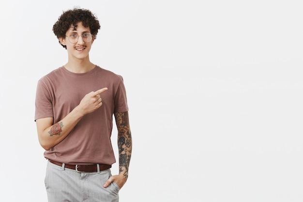 Ragazzo ebreo moderno ed elegante, tranquillo e fiducioso con baffi ricci e capelli scuri e tatuaggi sulle braccia rivolte a destra e sorridente amichevole che mostra la strada o indica un ottimo punto